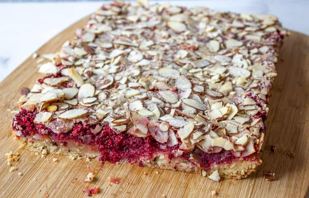 A large slab of cranberry bars on a wooden cutting board.