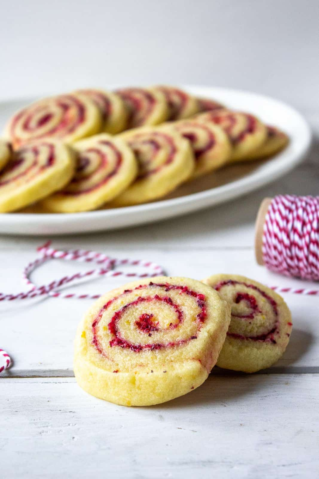 Cranberry filled cookies on a counter with a plateful of cookies in the background.
