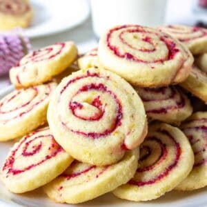 Cranberry pinwheel cookies piled on a plate.