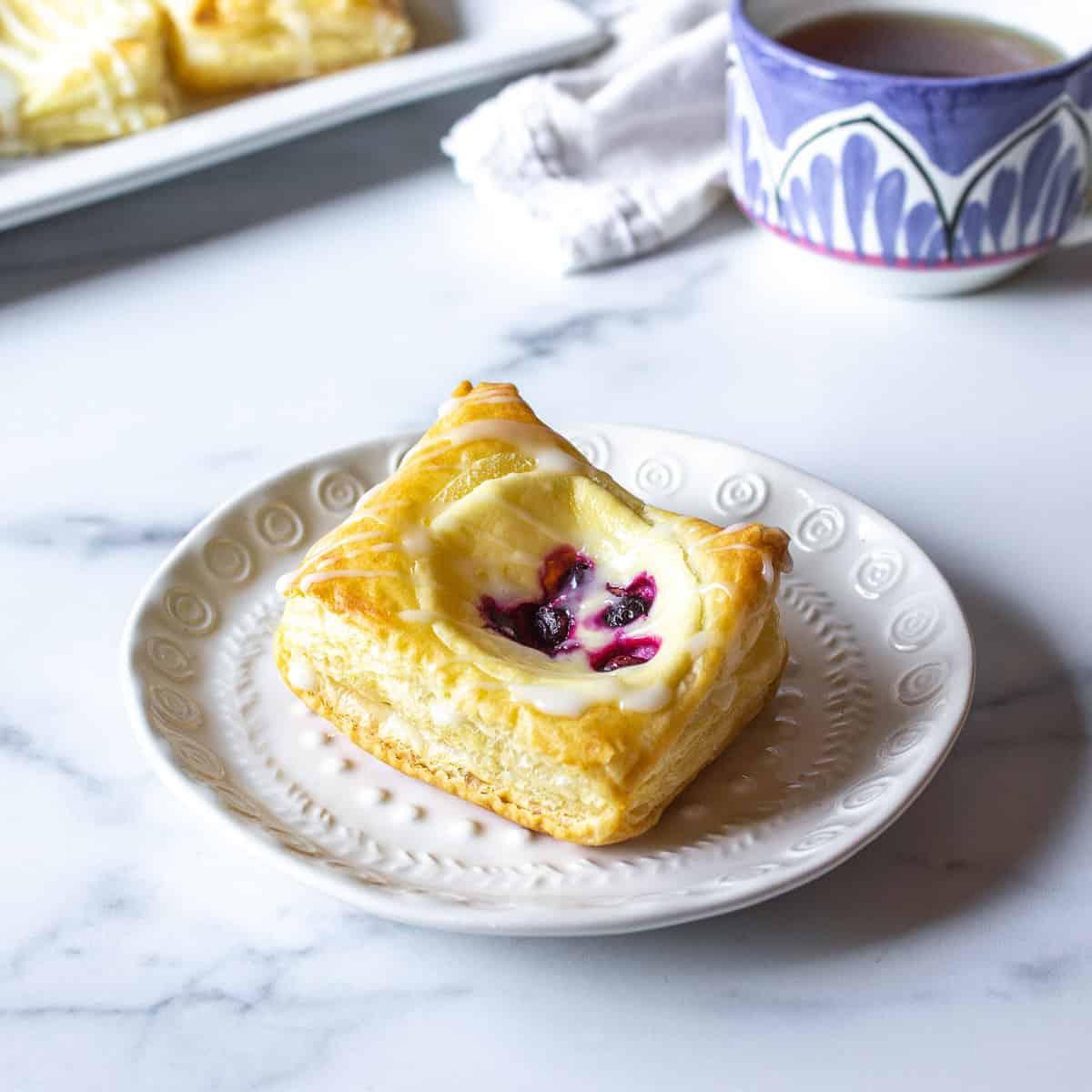 A danish filled with cream cheese and berries on a white plate.