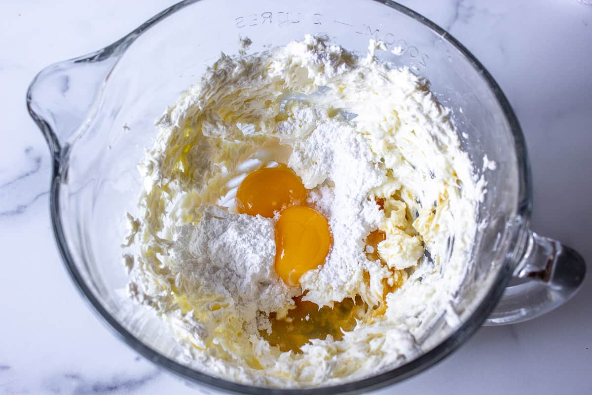 Cream cheese in a glass bowl with egg yolks, powdered sugar and vanilla.