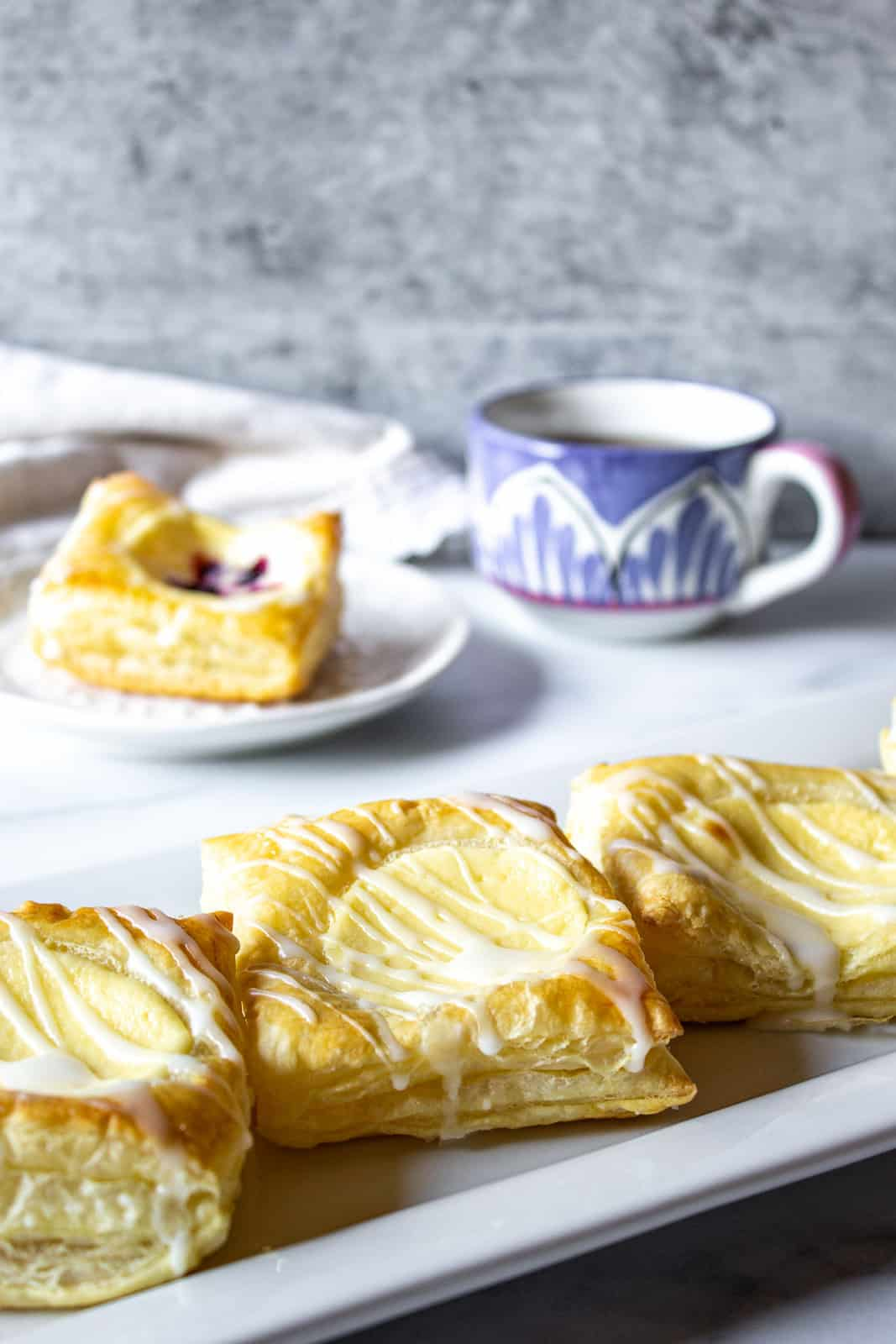 Cream cheese danishes on a white platter.