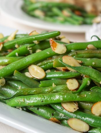 Brightly colored green beans topped with slivered almonds on a white platter.