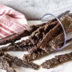 A pile of dried jerky on a white surface with a red and white towel.
