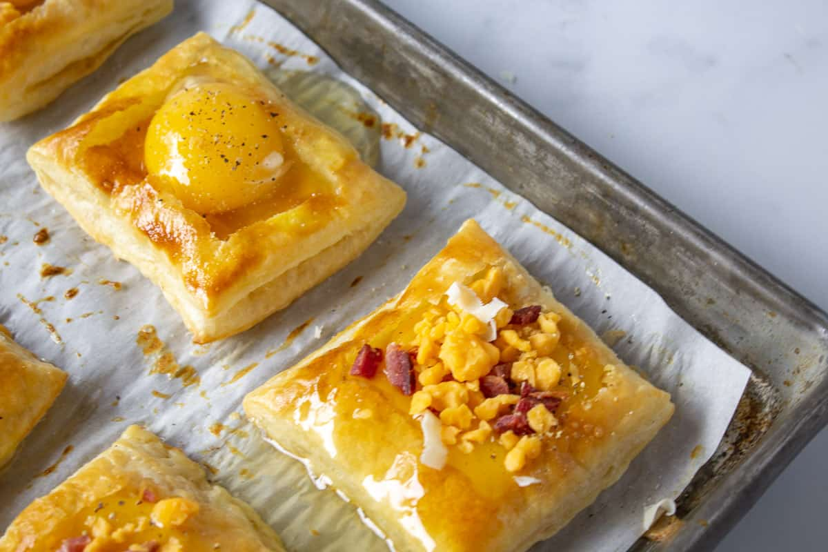 Puff pastry with raw egg topped with cheese and bacon.