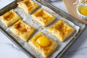 Puff pastry shells with a raw egg in one of the shells.