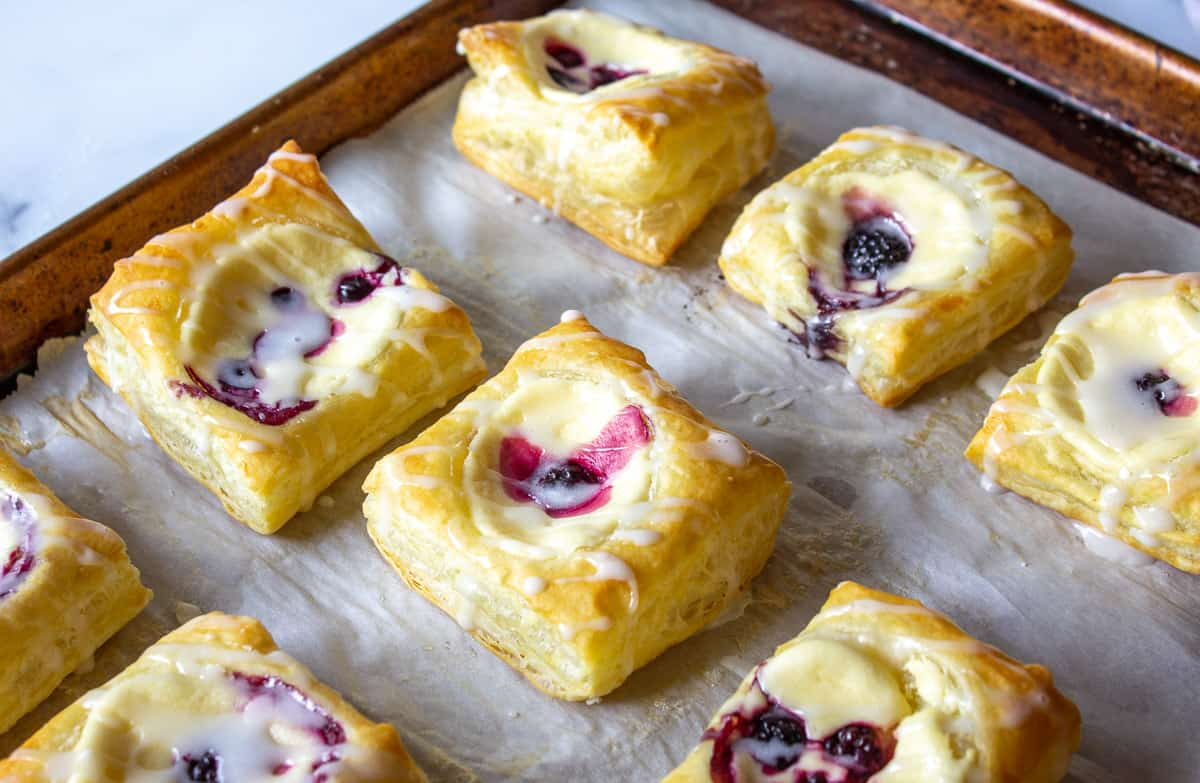 A baking sheet filled with danishes with cream cheese and berries.