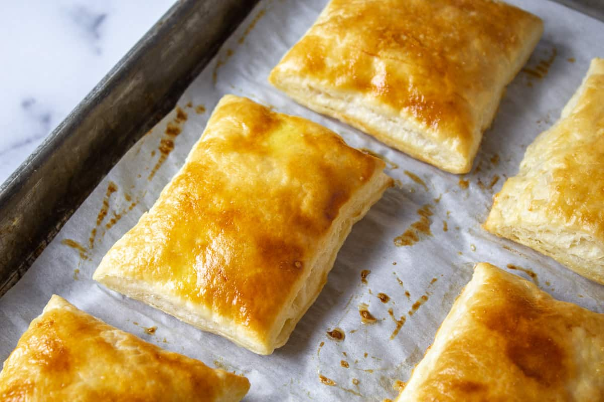 Puff pastry squares on a baking sheet.