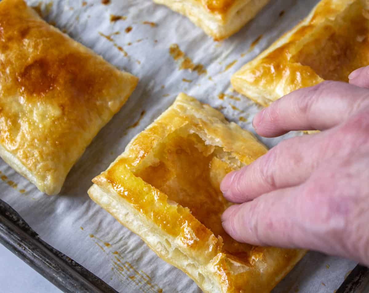 Finger tips pushing down the center of a puff pastry shell.