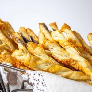 Puff pastry twists topped with sesame seeds in a metal basket.