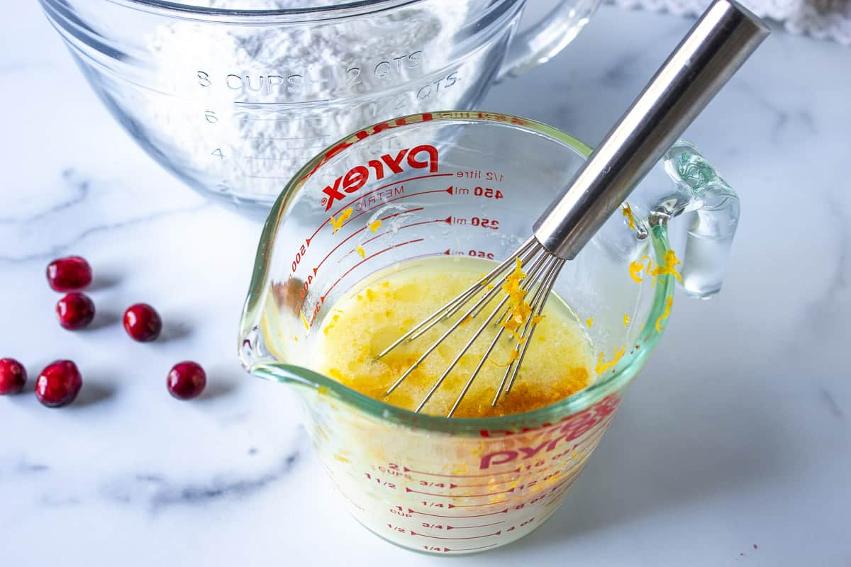 A glass measuring cup with a whisk and yellow liquid.