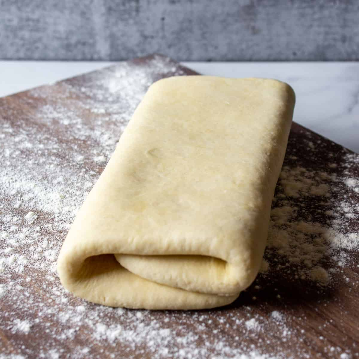 Folded puff pastry on a floured wooden board.