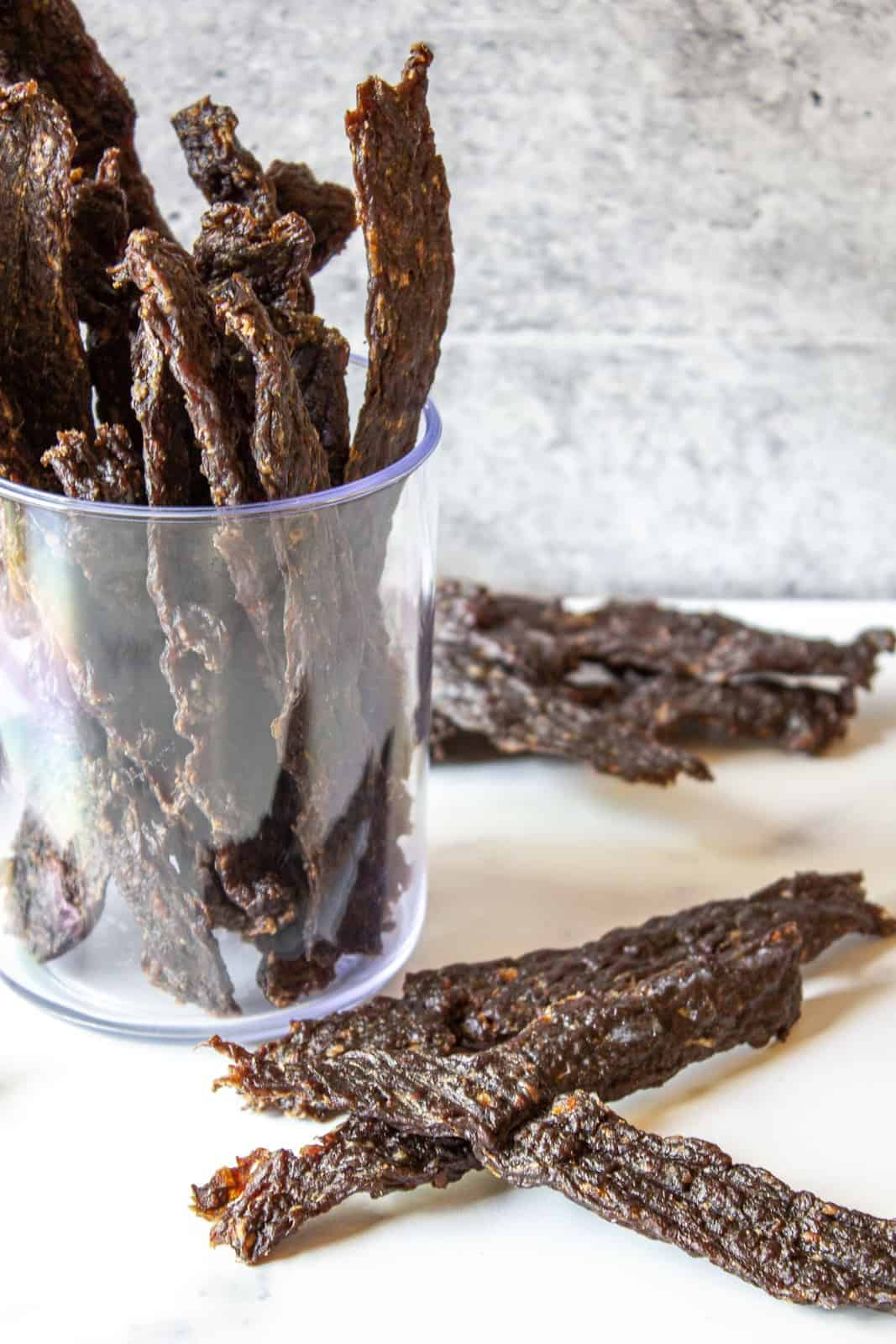 Dried jerky on a white surface with a jar filled of jerky in the background.