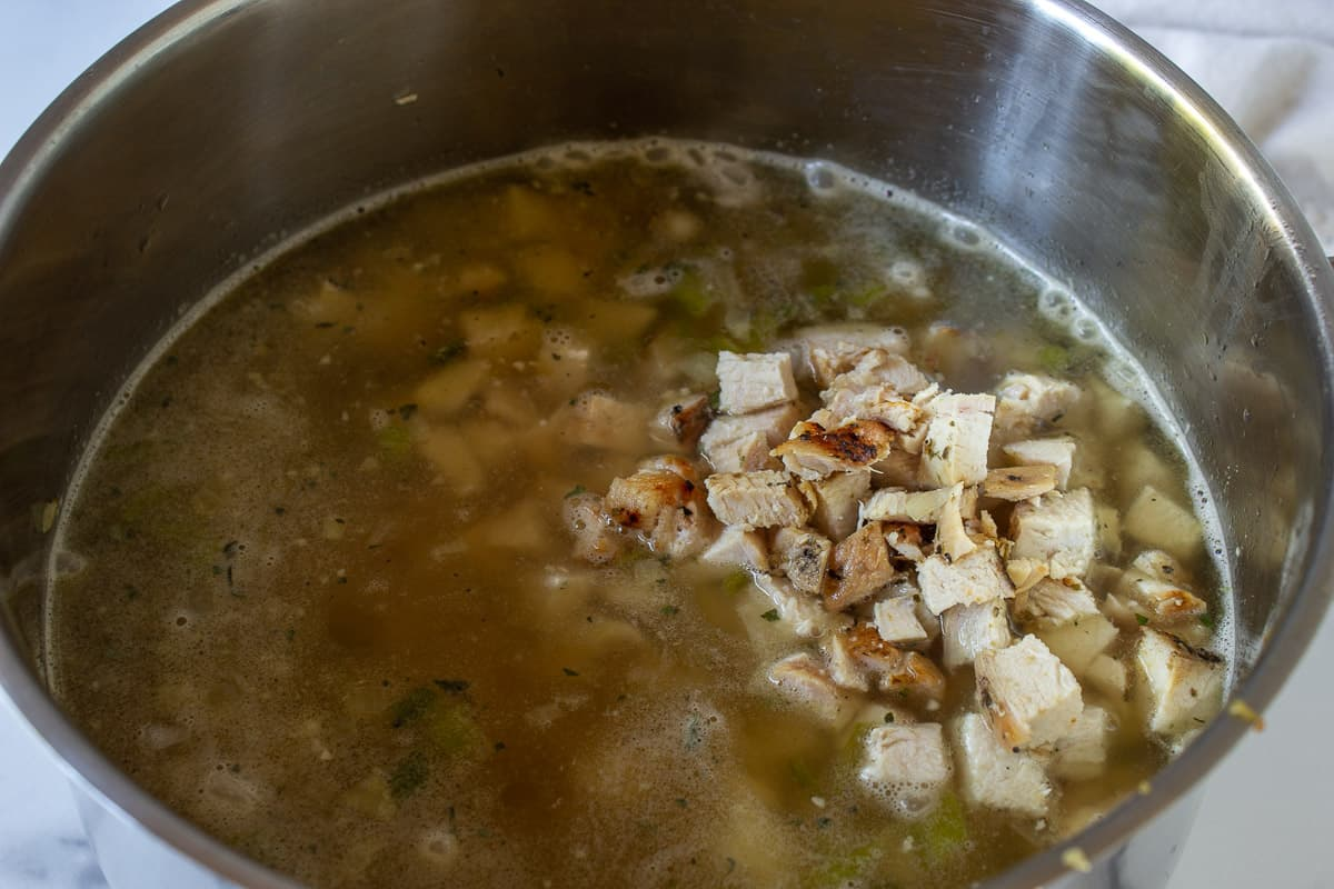 Chicken broth and chopped chicken in a large pot.