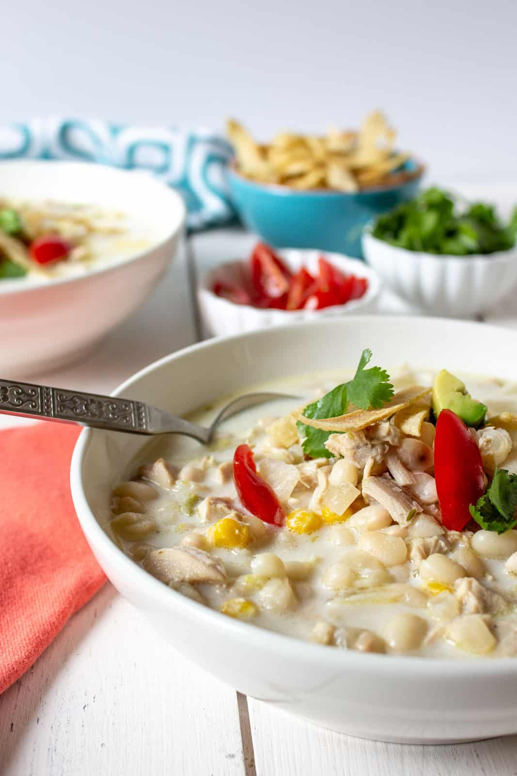 A bowl filled with white beans in a creamy broth and topped with fresh tomatoes and cilantro.