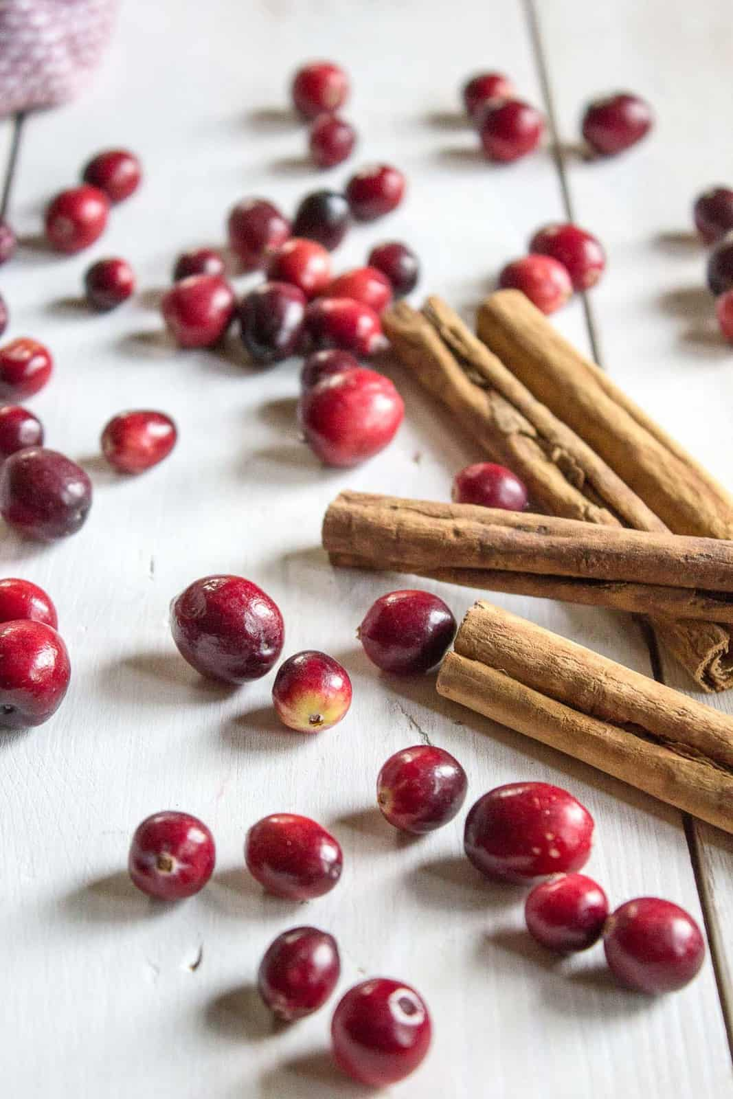 Fresh cranberries and cinnamon sticks scattered on a white board.