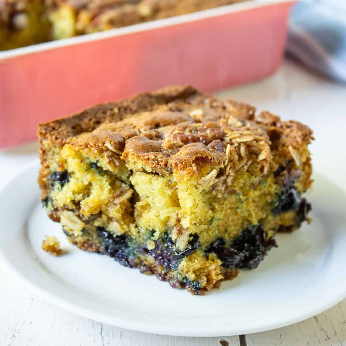 A slice of yellow coffee cake filled with blueberries.