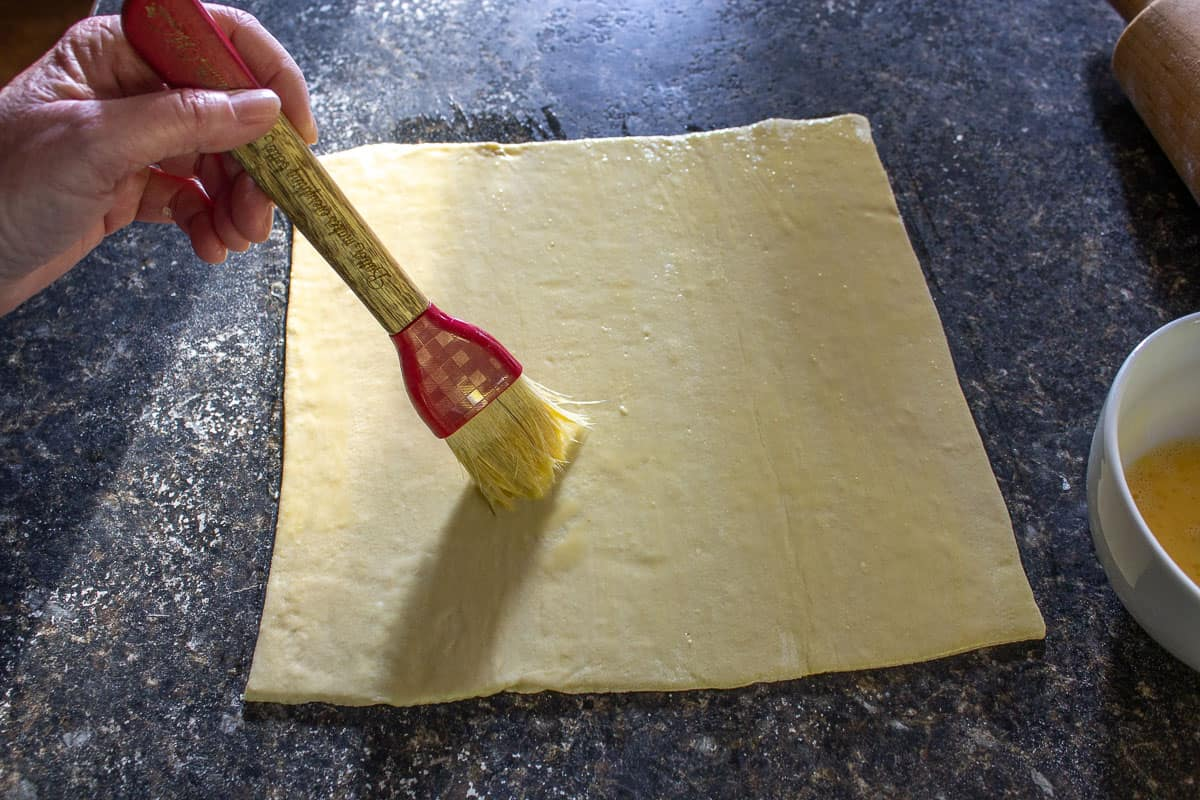 Puff pastry dough being brushed with an egg wash.