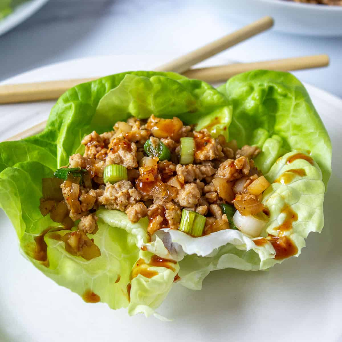 Bibb lettuce filled with cooked chicken and green onions.