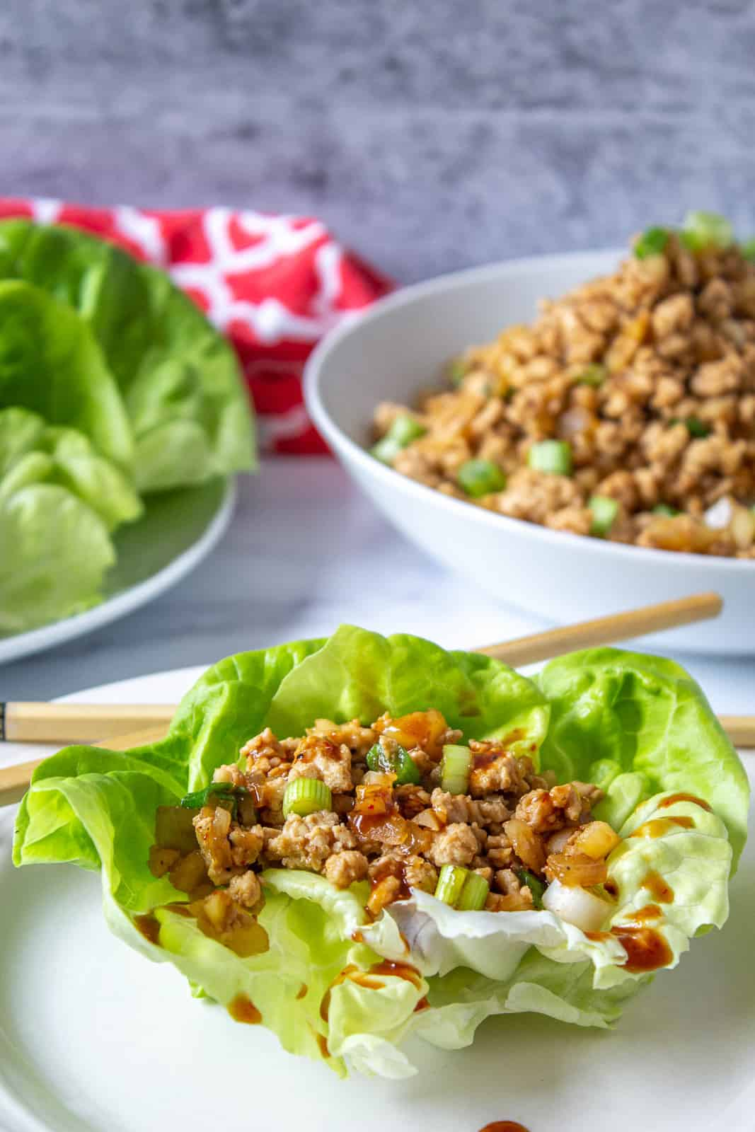 A lettuce leaf filled with chopped chicken and drizzled with a brown sauce.