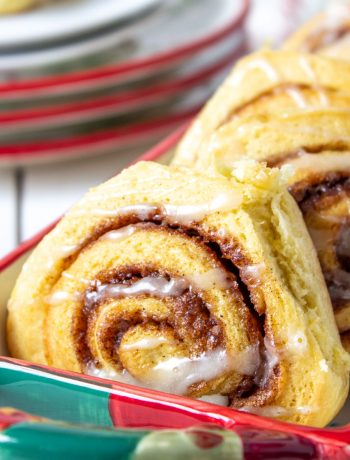 Cinnamon rolls stacked in a red and green dish.