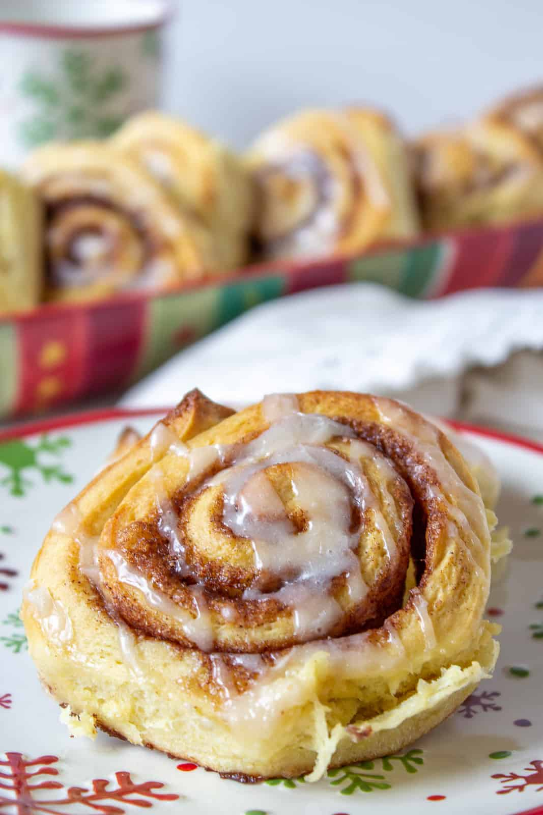 A cinnamon roll topped with a drizzled glaze.