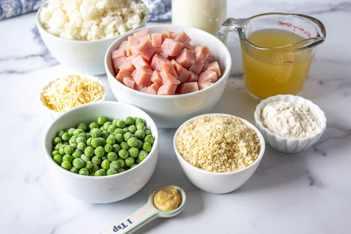 Small bowls filled with frozen peas, ham, rice, bread crumbs and seasonings.