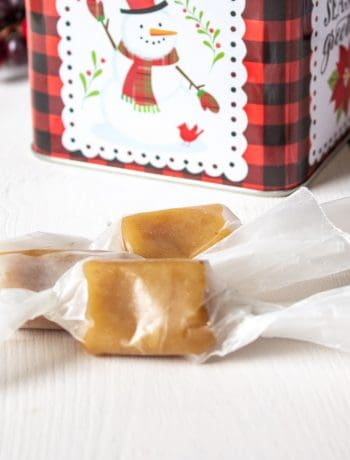 Caramels wrapped in waxed paper on a white board with a snowman tin behind the caramels.