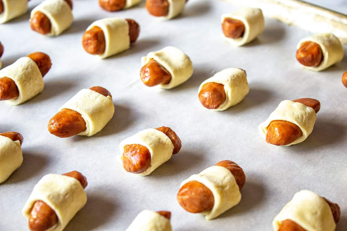 A cookie sheet filled with uncooked pigs in a blanket.