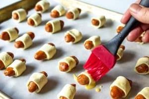 A red pastry brush adding an egg wash to little smokies wrapped in puff pastry.