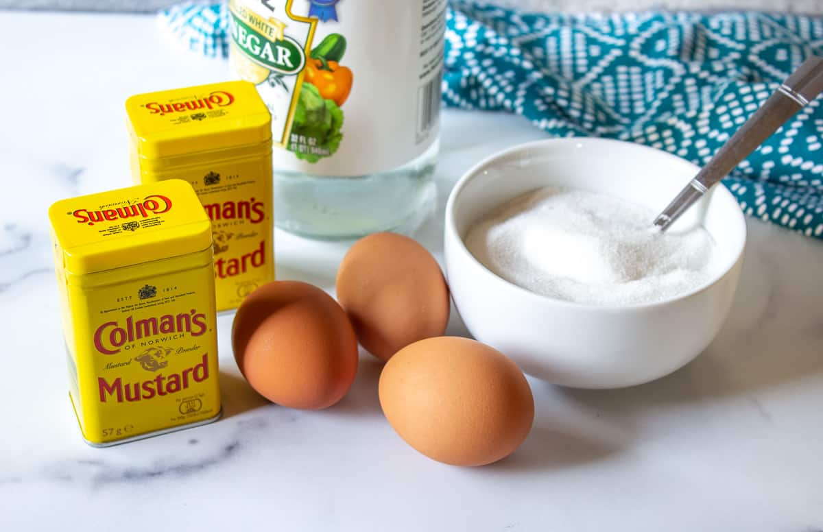 Jars of dried mustard, eggs and sugar arranged together on a white marbled surface.