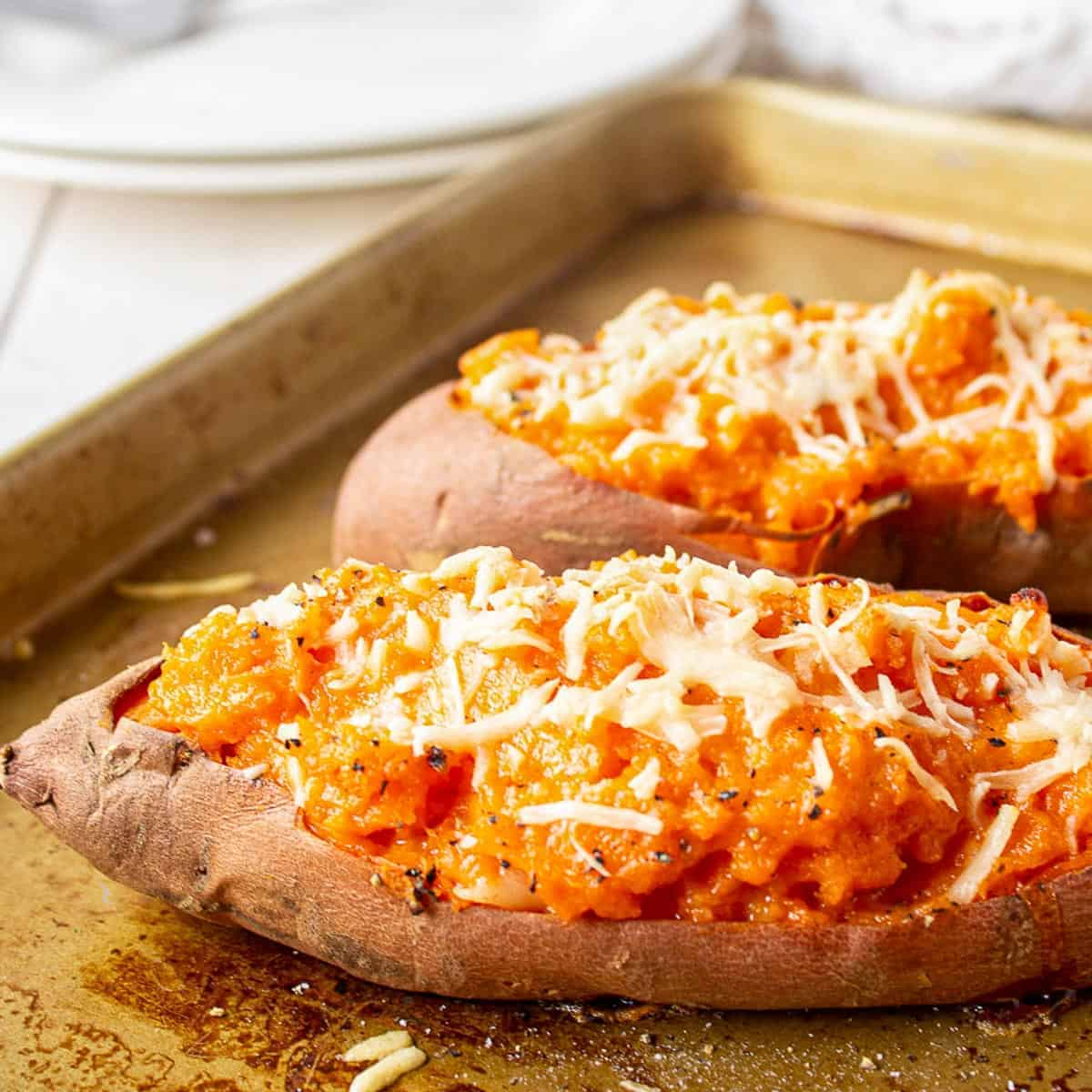 Sweet potato cut in half and filled with mashed sweet potatoes and topped with cheese.