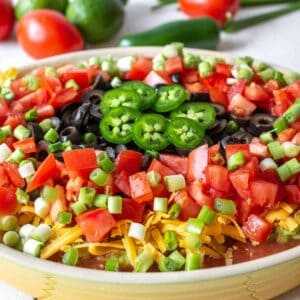 A layered dip topped with chopped tomatoes, olives and sliced jalapenos.