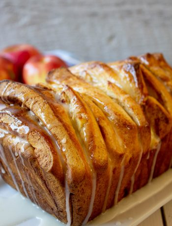 A loaf of pull apart bread with a white glaze drizzled across the top.