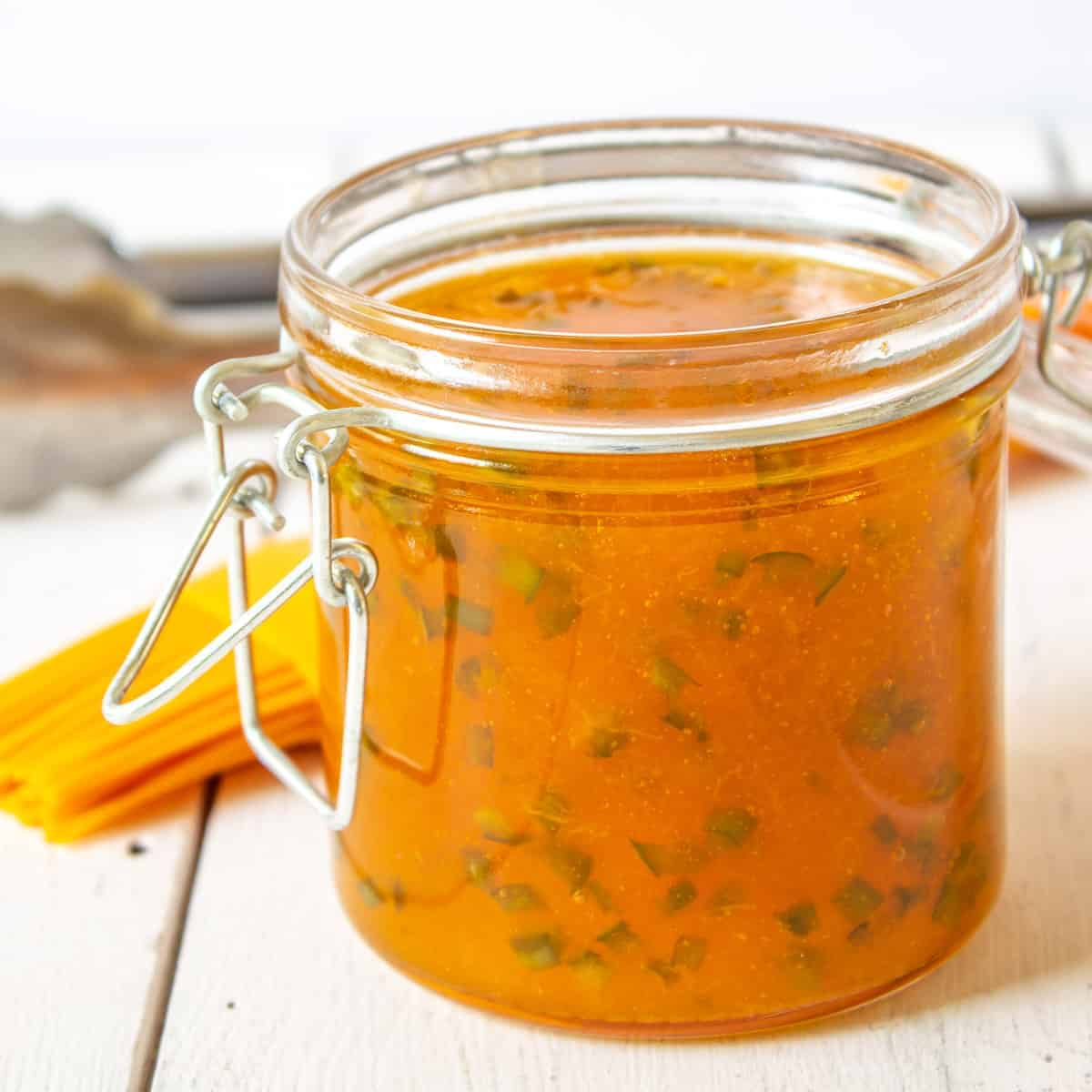 A glass jar filled with an apricot sauce with minced jalapenos.