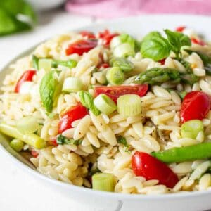 Orzo pasta with asparagus and tomatoes in a white bowl.