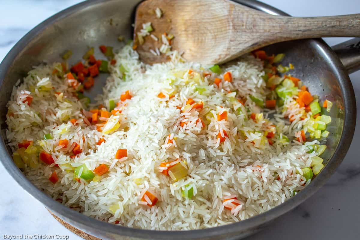 A sauté pan filled with rice, carrots and onions.