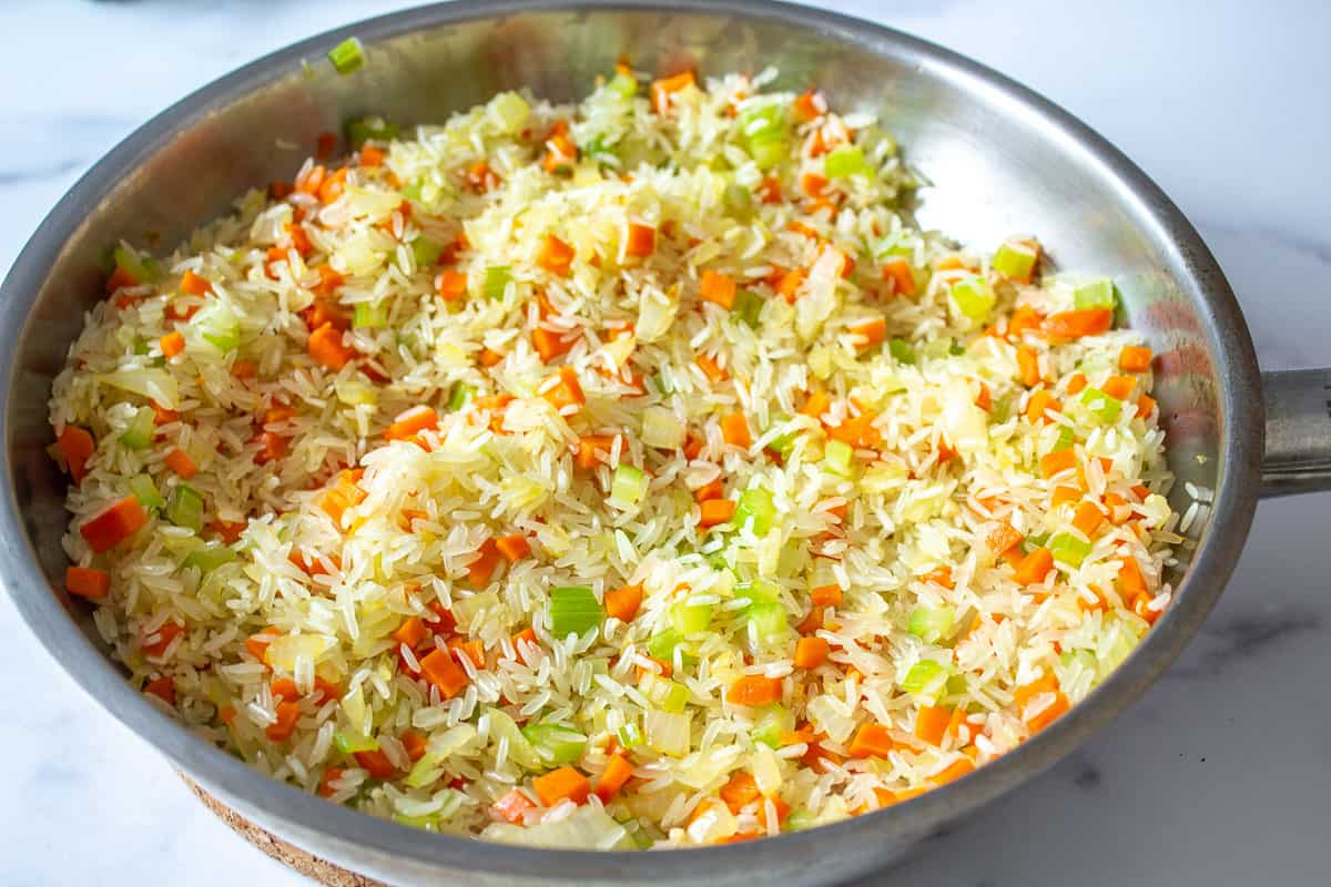 Onions, carrots and celery in a pan.