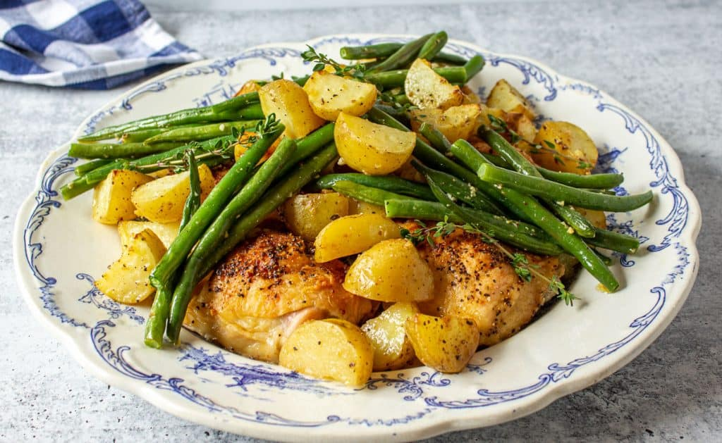 A blue and white plate filled with chicken, potatoes and green beans.