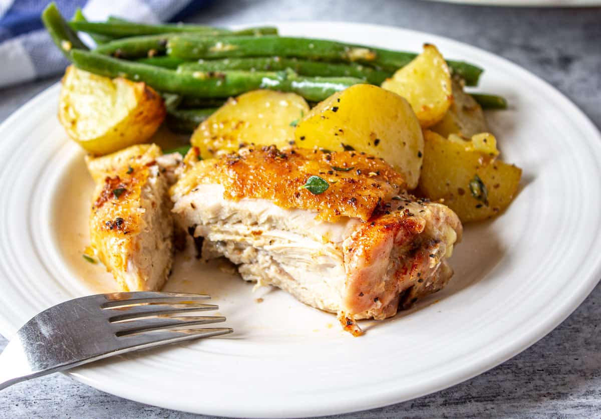 Cut chicken thigh on a plate with potatoes and green beans.