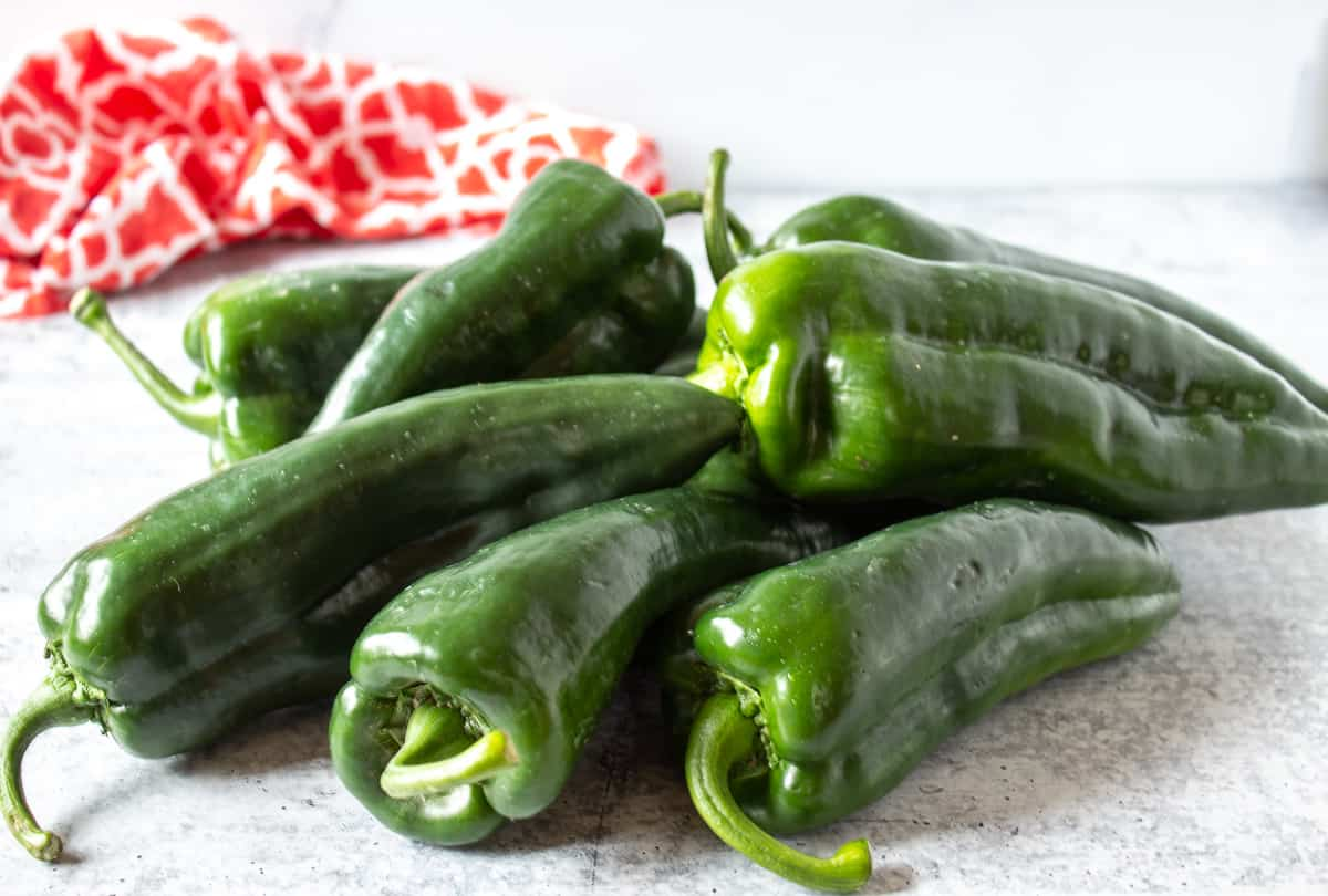 Poblano peppers piled in a stack  on a countertop.