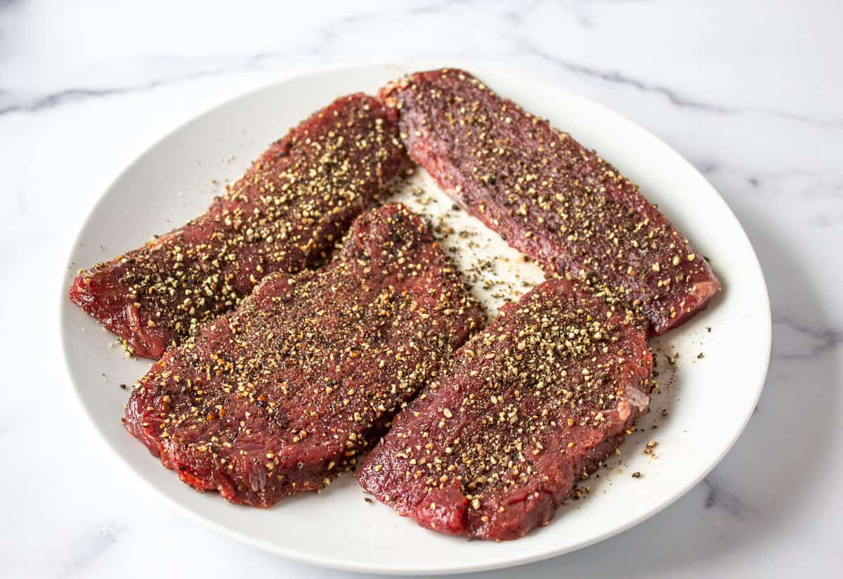 Steaks covered with crushed pepper.