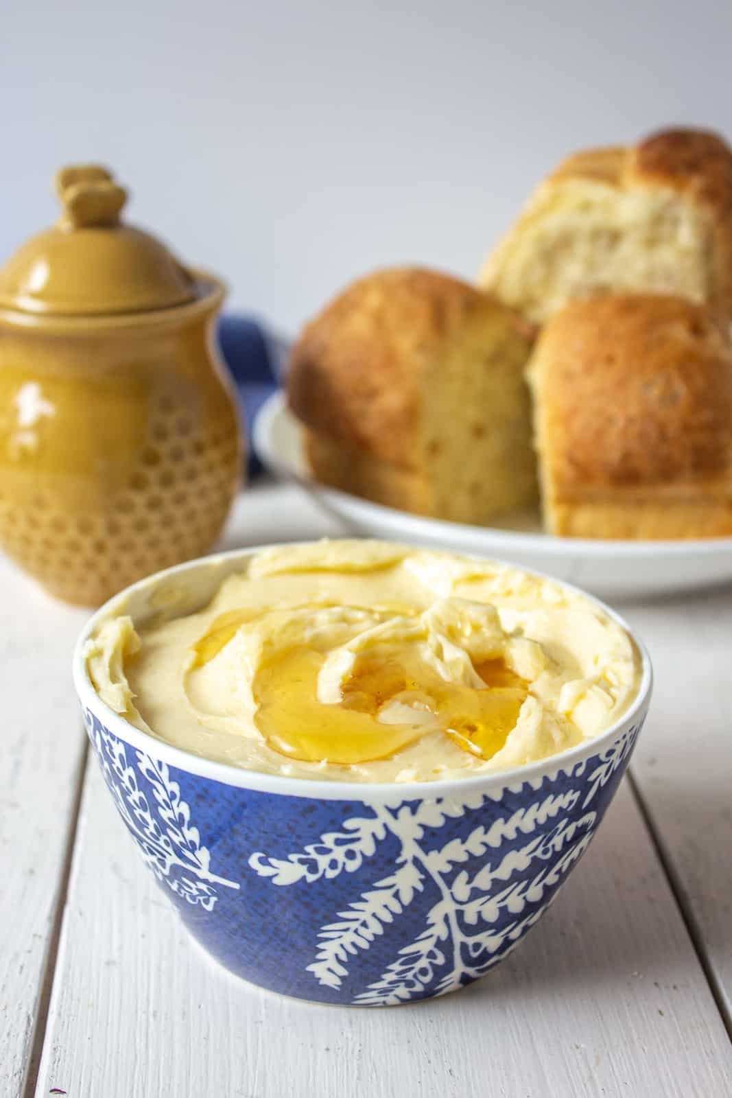 A small blue and white bowl filled with whipped butter and topped with honey.