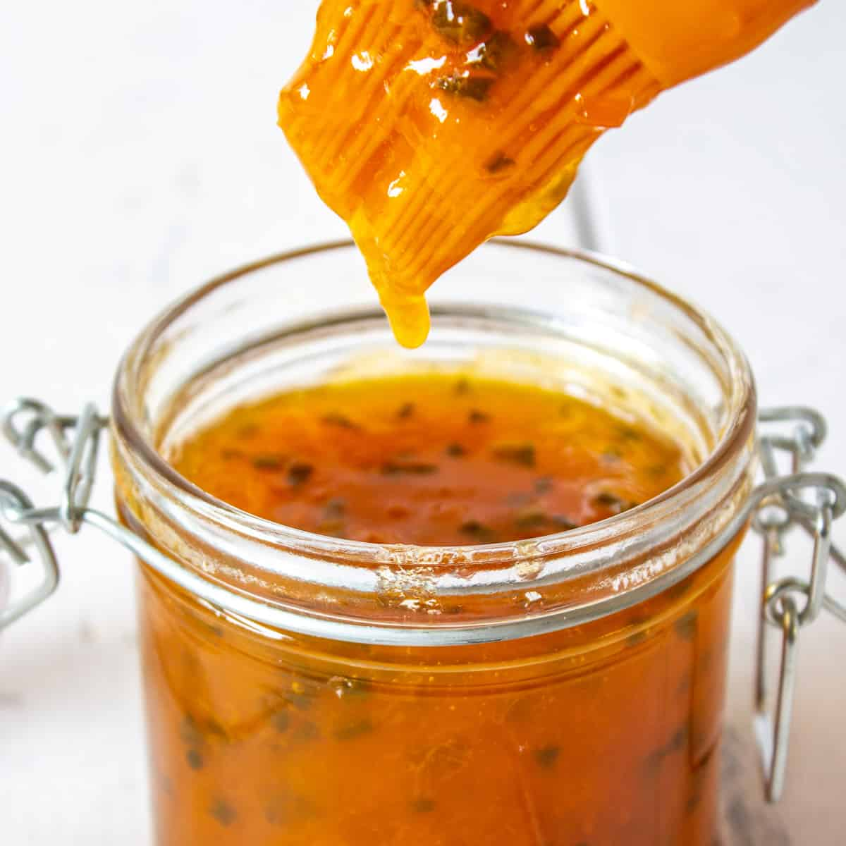 A basting brush dripping with an apricot sauce over a jar filled with the sauce.