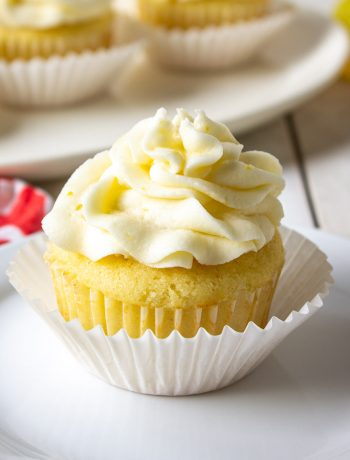 A lemon cupcake topped with a swirl of frosting on a white plate.