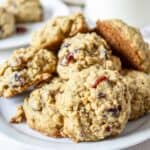 A plate filled with a stack of oatmeal cookies with cranberries.