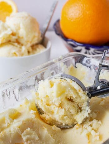 Orange ice cream in a glass dish being scooped into a round shape by an ice cream scoop.
