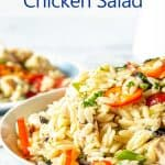 Orzo pasta with chunks of chicken and slices of bell pepper in a bowl.