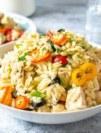 A bowl filled with orzo, bell peppers, tomatoes and chicken.