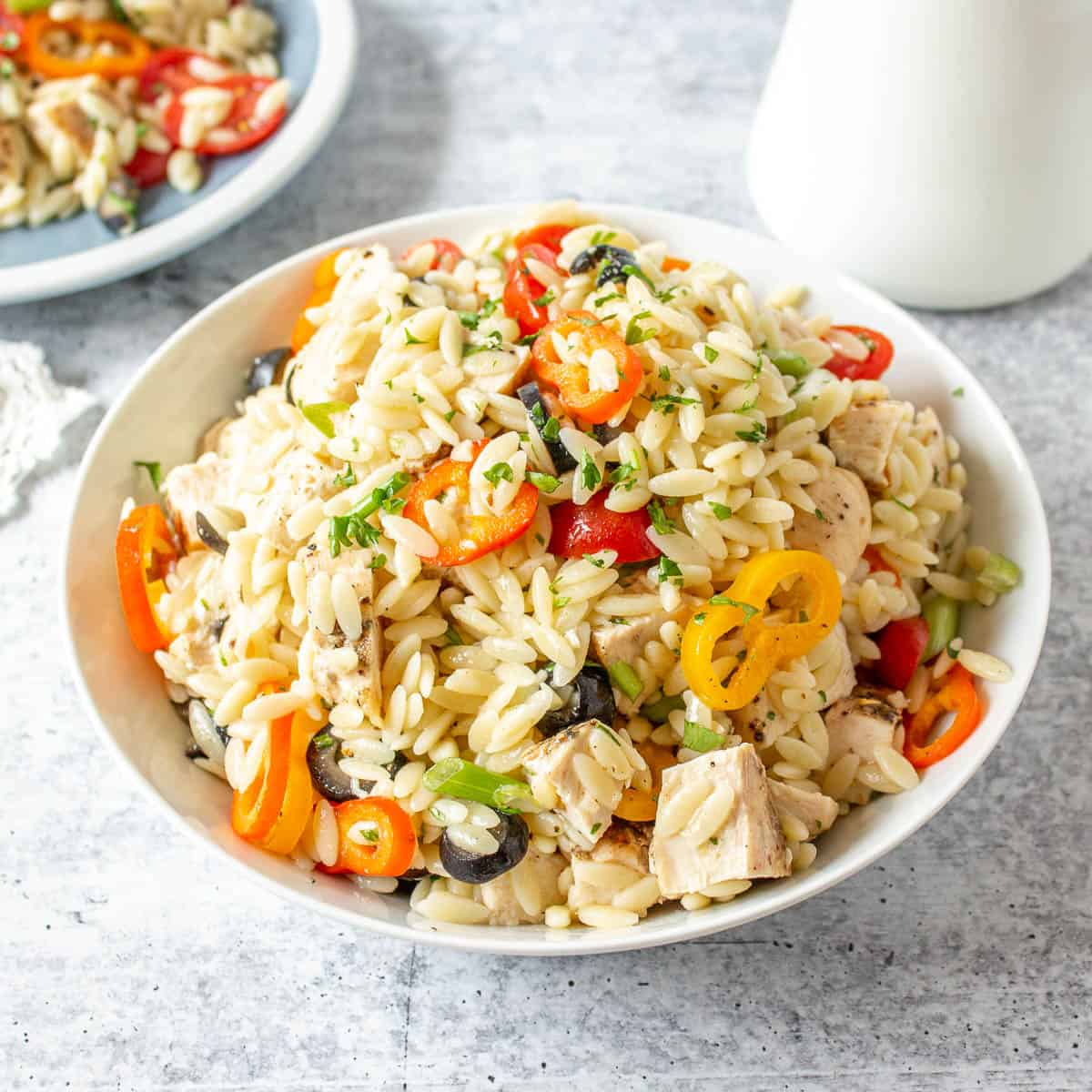 A bowl filled with orzo pasta, sliced tomatoes and chunks of chicken.